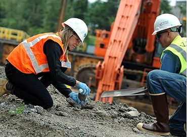 Environmental assessment and compliance - two people in hard hats working outside