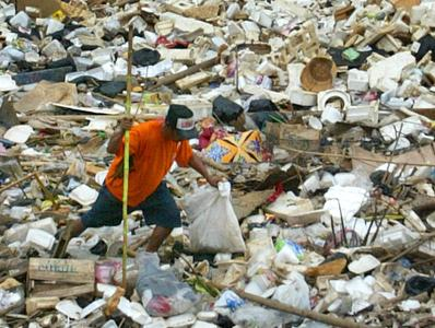 Landfill insurance claim support - man picking up trash in a landffill
